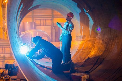 Two welders work in a pipe for an oil pipeline.